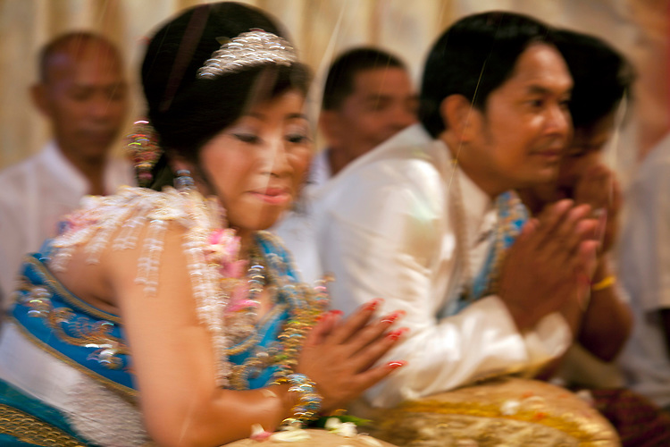 Bride and groom are showered with rice at a buddhist wedding in a small village outside of Phnom Penh, Cambodia. <br /> <br /> Photos &copy; Dennis Drenner 2013.
