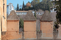 Crenellated ramparts of the Alhambra, and behind, the Generalife, summer palace and country estate and gardens of the Nasrid kings, built in the 14th century under Muhammad III, 1302–1309 and redecorated by Abu I-Walid Isma'il, 1313-1324, Alhambra Palace, Granada, Andalusia, Southern Spain. The Alhambra was begun in the 11th century as a castle, and in the 13th and 14th centuries served as the royal palace of the Nasrid sultans. The huge complex contains the Alcazaba, Nasrid palaces, gardens and Generalife. Granada was listed as a UNESCO World Heritage Site in 1984. Picture by Manuel Cohen