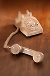 A vintage rotary dial telephone sits on a wooden desk with the handset removed.  The handset is in the foreground as though someone was on hold. The foreground and background are blurred.