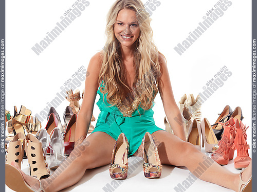 Happy smiling young beautiful woman sitting surrounded with many different fashionable shoes isolated on white background.