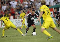 WASHINGTON, DC - AUGUST 4, 2012:  Dwayne DeRosario (7) of DC United moves past Carlos Mendes (4) of the Columbus Crew during an MLS match at RFK Stadium in Washington DC on August 4. United won 1-0.