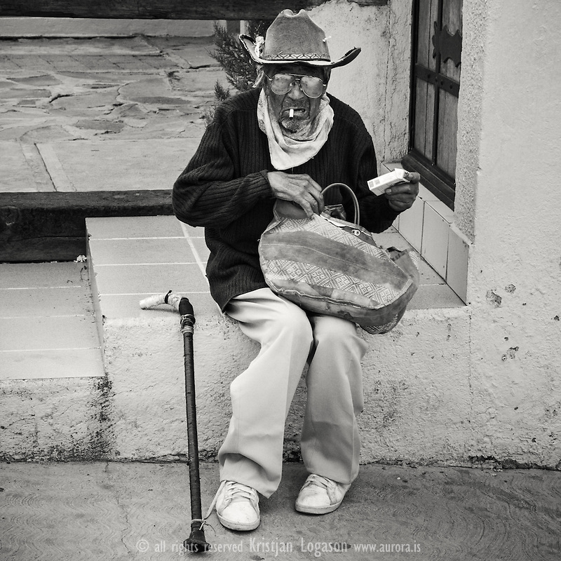 Old man in San Miguel de Allende with nylon bag in hand having a sigarett and a rest on house steps
