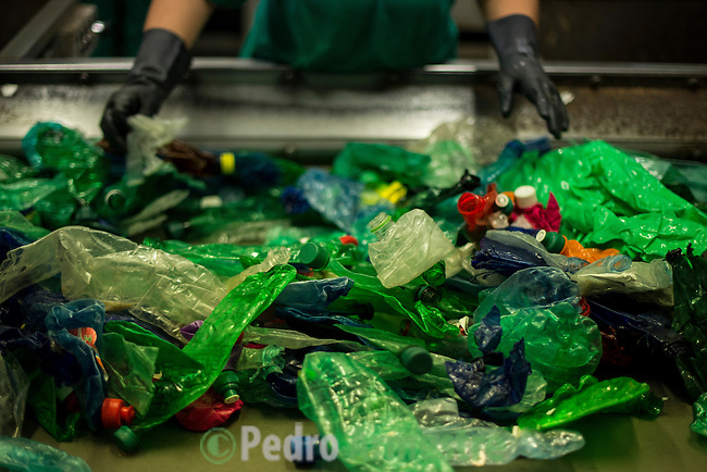 """An employee sorts plastic waste collected in the sea by fishermen at a plastic processing plant in Chiva, near Valencia on November 3, 2015. Ecoalf, a Spanish Madrid-based firm founded in 2010, has already launched """"a new generation"""" of clothes and accessories made from plastic bottles, old fishing nets and used tires found on land. © Pedro ARMESTRE"""