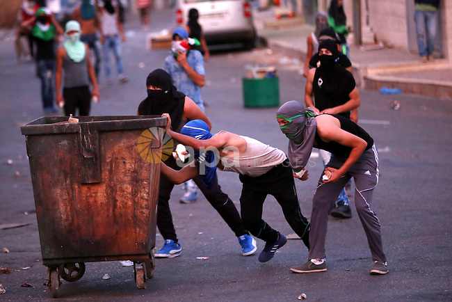 Palestinian protesters take cover during clashes with Israeli security forces over the Al-Aqsa mosque compound, close to the Israeli manned checkpoint of Hezma in the Israeli occupied West Bank, between Jerusalem and and the Palestinian city of Ramallah on September 30, 2015. The compound has been the scene of repeated clashes in recent weeks, provoking international calls for calm at the highly sensitive site which is the third holiest in Islam but is also known to Jews as the Temple Mount, the most sacred in Judaism. Photo by Shadi Hatem