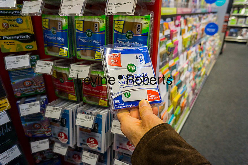 A shopper chooses a Green Dot brand debit card in a store in New York on Tuesday, October 11, 2016. The Consumer Financial Protection Board has issued new rules for the prepaid debit card industry giving users many of the same protections once available only to credit card users. (© Richard B. Levine)