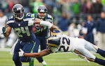 Seattle Seahawks running back Marshawn Lynch (24) breaks the tackle of St. Louis Rams cornerback Trumaine Johnson (22) in the third quarter at CenturyLink Field in Seattle, Washington on December 29, 2013.  Seahawks clinched the NFC West title and home-field advantage throughout the playoffs with a 27-9 victory over the St. Louis Rams.  Lynch rushed for 97yards on 23 carries and scored one touchdown in the win.  ©2013. Jim Bryant Photo. ALL RIGHTS RESERVED.