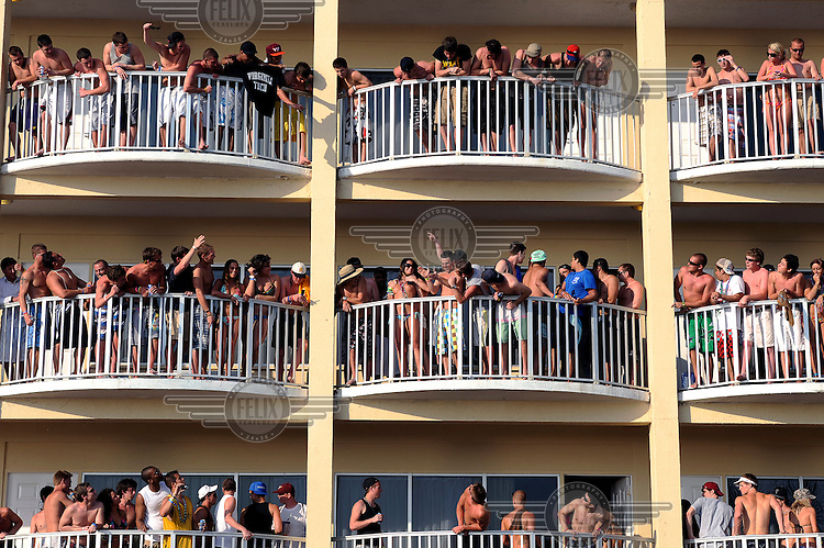 Students cheer as a girl goes topless on a hotel balcony during Spring Break on Panama city beach in Florida.