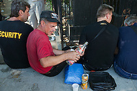 Moscow, Russia, 25/07/2010..A man pours vodka shots as hundreds of Russians gather at the grave of legendary bard singer, poet and actor Vladimir Vysotsky to mark the 30th anniversary of his death. Vysotsky, an alcoholic and heroin addict who died in 1980 aged 42 of a heart attack, is best known for his songs of Soviet prison and military life, and his acting on stage and screen. Much of his work was officially unpublished during his lifetime, and he remains a potent anti-authoritarian symbol of protest to Russians of all ages even today.