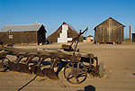 Wooden barns and sheds, rusting old metal and wood gang plow sits along the roadside in the San Joaquin Valley of California.