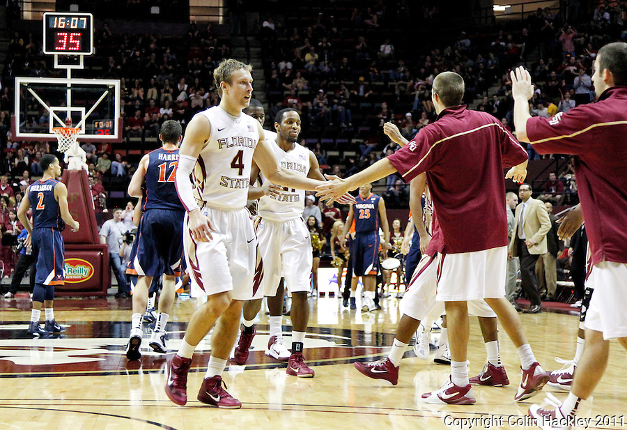 TALLAHASSEE, FL 10-FSU-VA MBB11 CH-Florida State's Deividas Dulkys, left, and Michael Snaer celebrate with teammates after stretching the Seminole's lead against Virginia during second half action Saturday at the Donald L. Tucker Center in Tallahassee. The Seminoles beat the Cavaliers 63-56...COLIN HACKLEY PHOTO