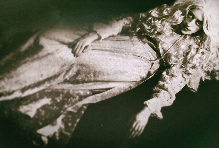 A woman in a white gown, with a pale complexion and white hair, laying on the ground, staring at the viewer..