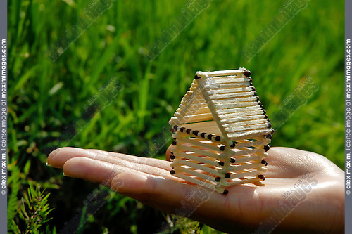 House made from matches on a female hand in green grass nature environment. Home renovation, future house, real estate, housing, property insurance concept