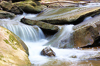Water flows smoothly amongst the rocks in a fast moving stream