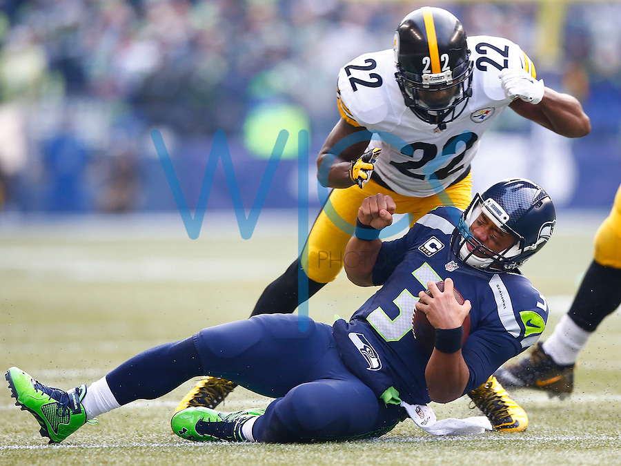 Russell Wilson #3 of the Seattle Seahawks slides to avoid a tackle by William Gay #22 of the Pittsburgh Steelers in the first half during the game at CenturyLink Field on November 29, 2015 in Seattle, Washington. (Photo by Jared Wickerham/DKPittsburghSports)