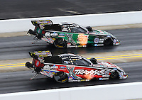 Sep 14, 2014; Concord, NC, USA; NHRA funny car driver John Force (top) defeats daughter Courtney Force during the Carolina Nationals at zMax Dragway. Mandatory Credit: Mark J. Rebilas-USA TODAY Sports