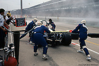 Roger Penske uses a signal board to communicate with Bobby Unser during a pit stop in the 1981 Indianapolis 500.