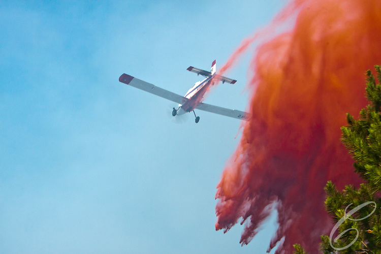 An aerial firefighting plane drops retardant on the Dyer Mill fire in Grimes County, Texas on June 21, 2011.