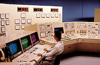Operator at control console in control room in conventional power station.