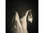 A ghostly woman, veiled in white, holding a lantern nd looking at it.