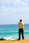 A senior citizen stands next to the ocean.  He has his arms folded and is wearing slacks and a long sleeved shirt. He seems out of place on the beach.