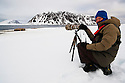 Norway, Svalbard, tourist sitting in snow photographing walruses