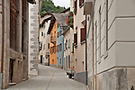 A couple walks down the cobble stone main street in the small town of Castasegna, a Swiss town right on the border with Italy in the Bregaglia Valley