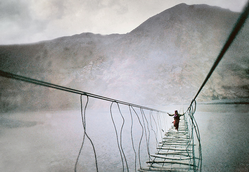 An old Wakhi woman crosses a suspended bridge over the Hunza river in Gojal region, near Hunza, Northern Pakistan.