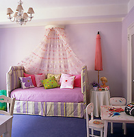 This pretty girl's bedroom uses designer fabrics and colourful patterned cushions