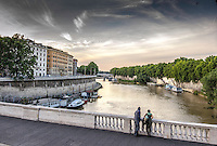 Fine Art Print Photograph. A romantic river scene of the Tiber river in the ancient city of Rome. The lighting of the day reveals the subtle textures of the river water, and the historical building that gracefully line the fortified walls of the river shoreline.