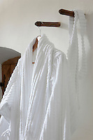 Detail of a white toweling dressing gown hanging from a wooden peg