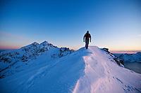 Person hikes along snow covered ridge of Stamsundheia with Steinstind peak in distance, Stamsund, Vestvågøy, Lofoten islands, Norway