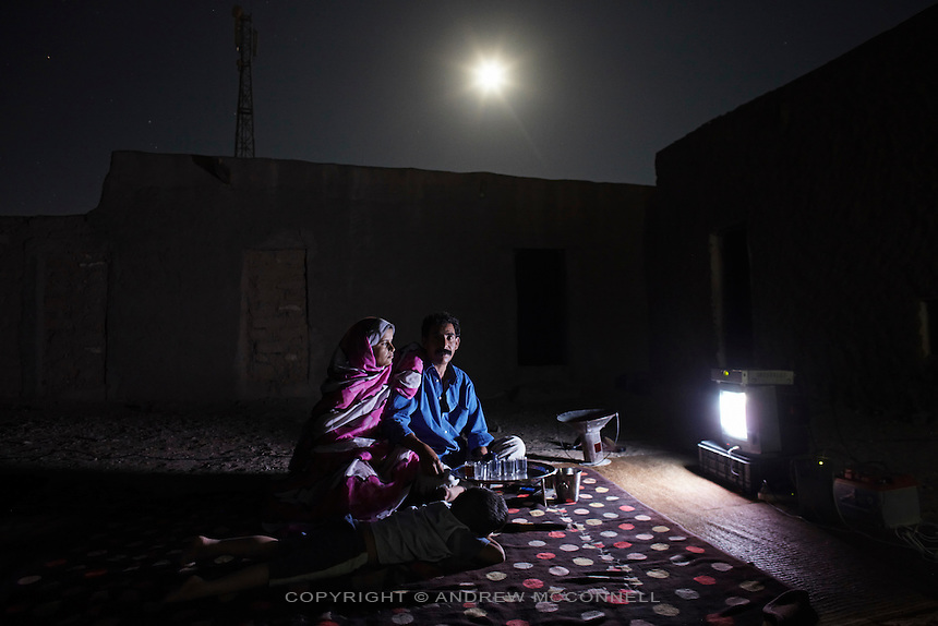 Ali Salem Salma, 41, statistician for the Saharawi government, pictured watching TV at home with his wife, Nabba, and four year old son, Khadda, in Smara refugee camp, Algeria...I was born in El Aaiún in October 1968. In 1975 we built a house in Zemla, a neighbourhood of the city. At the end of 75 Morocco invaded our cities during the 'green march' and the Moroccan soldiers told us to leave our house. Moroccan civilians moved into all the homes. We spent six months travelling to Algeria to the refugee camps and we are still here. We still have a key to our house we even have papers to prove it belongs to us. When we first came to Algeria there was nothing here and I remember many children dying. Many families sent their children away to study in different countries, even children who were only three years old. ..I went to Libya in 1976 with a lot of other boys and girls, about eight hundred. We took buses for many days and arrived in Tripoli. They were good to us and really helped us with food and clothes and educated us very well. I went to university in Algeria and in 1992 graduated with a degree in statistics and returned to the camps to work for the Saharawi government. Our lives here are simple, we know there are better ways to live but we must be very well organised in order to survive here. Now I send my children to school and maybe they can travel to study at a university but even if they get a degree they will return here and have nothing because there is no possibility of a job...I know we agreed to a ceasefire and the international circumstances have obliged us to respect it. But I believe, and I am not the only one, that the only way to get our freedom is by war. We know the UN cannot impose anything and are a weak organisation. Most of their decisions are not applied or listened to. We are here in this land and it does not belong to the Saharawi and everybody knows we will not integrate or be part of Morocco. We believe the only organisation is the Fren