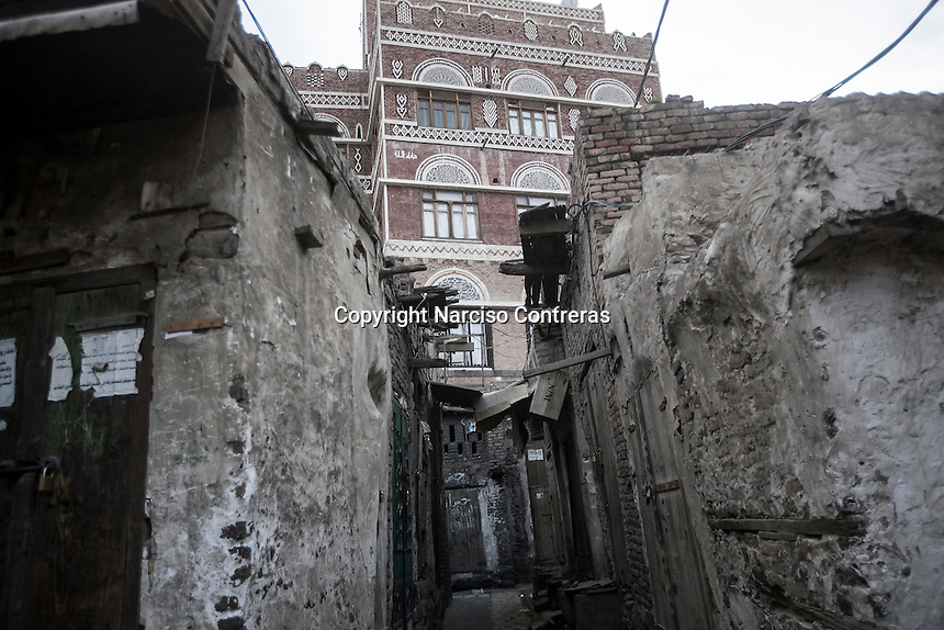 Monday 13 July, 2015: A classical-style tower-house is seen at the bottom of empty narrow streets in the Old City of Sana'a, a 2,500-year-old cultural heritage site endangered after a fighter jet of the Saudi-led coalition bombed and destroyed a line of residential tower-houses killing 4 residents and reducing to rubble the historial site. The ongoing aerial campaign of bombardments by the Arab states and their western allies led by Saudi Arabia and the heavy fighting against the entrenchment of the Houthi insurgency along the Yemeni main cities from north to south has caused an international alert for the enlisted cultural heritage sites in Yemen, such as the historic town of Zabid, the Old City of Sana'a and the Old Walled City of Shibam. (Photo/Narciso Contreras)