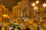 Even at night, the Trevi Fountain (Rome, Italy) is busy with after-dinner visitors by streetlight.
