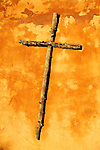 The golden light of sunset illuminates a cross constructed from latillas. Taos, New Mexico.