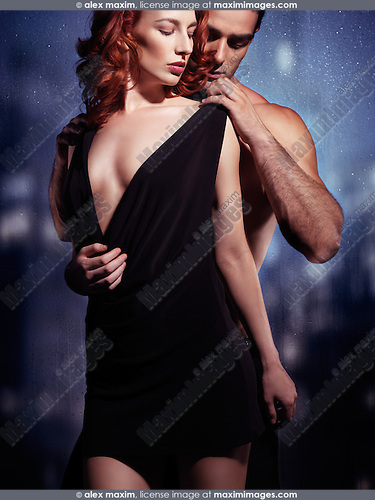 Sensual couple portrait of a man taking off woman's dress