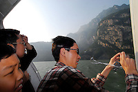 "Tourists look at the Wu Gorge from the window of a hydrofoil whilst travelling up the Newly formed ""ribbon lake"" of the Yangtze River in China. The construction of the Three Gorges Dam and rise in water level of around 100 meters, creating a narrow lake 450 km in length and  has resulted in the relocation of around 1.5 million people. All of their homes have been destroyed. The Dam is now completed and the water will rise a further 35 meters this fall..16 May 2006"