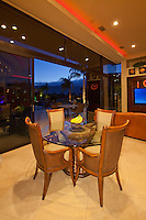 Night time view of dining table and chairs in modern home in fron of open glass doors