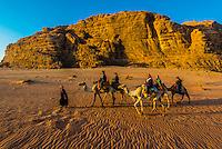 Tourists on a a camel ride, Arabian Desert, Wadi Rum, Jordan.