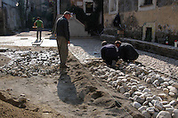 Operai mentre sistemano una strada lasticata in pietra. Workers  while settle a road paved in stone...