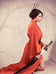 Beautiful asian woman in red kimono kneeling with an unsheathed katana sword