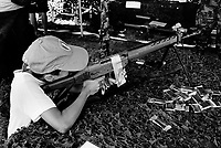 Switzerland. Canton Fribourg. Estavayer. A young boy is playing with an automatic or semi-automatic assault rifle <br /> SG 550 at a swiss army stall during the Federal Wrestling and Alpine Games Festival. The SG 550 is an assault rifle manufactured by Swiss Arms AG (formerly Schweizerische Industrie Gesellschaft) of Neuhausen, Switzerland. &quot;SG&quot; is an abbreviation for Sturmgewehr, or &quot;assault rifle&quot;. The rifle is based on the earlier 5.56mm SG 540 and is also known as the Fass 90 or Stgw 90. An assault rifle is a selective-fire rifle that uses an intermediate cartridge and a detachable magazine. 27.08.2016 &copy; 2016 Didier Ruef