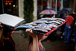 Vendors use their board of political buttons as shelter as it begins to rain a day before the 2012 Democratic National Convention in Charlotte, N.C. on Sept. 3, 2012.  Photo by Greg Kahn