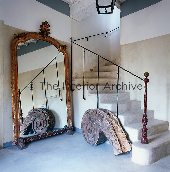 A country hallway with a stone staircase with an iron newel post on the bottom step. A large gilt-framed mirror standing against one wall lends a sense of space to the room.