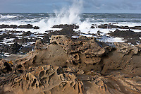 Tafoni etched sandstone at  Bean Hollow State Beach with Pacific waves slamming into the rocky Central California Coast.