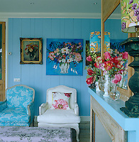 The inspiration for the vivid blue colour scheme came directly from the naive flower paintings hanging above the two antique armchairs in the living room