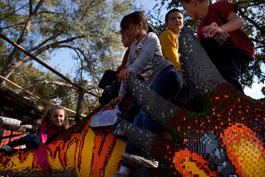 Children play on a lego dinosaur in front of Coastersaurus roller coaster in the new theme park Legoland in Whitehaven, Florida on February 11, 2012.