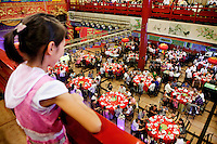 A young girl looks down from a balcony at the guests as they eat and drink in the main dinning hall at The West Lake Restaurant. Able to seat up to 5,000 people at one sitting, The West Lake Restaurant is the biggest Chinese restaurant in the world. Each week its diners, who staff are taught are 'the bringers of good fortune', devour 700 chickens, 200 snakes, 1,200 kgs of pork and 1,000 kgs of chillis. Its 300 chefs cook in five kitchens and its staff total more than 1,000.It is fully booked most nights.