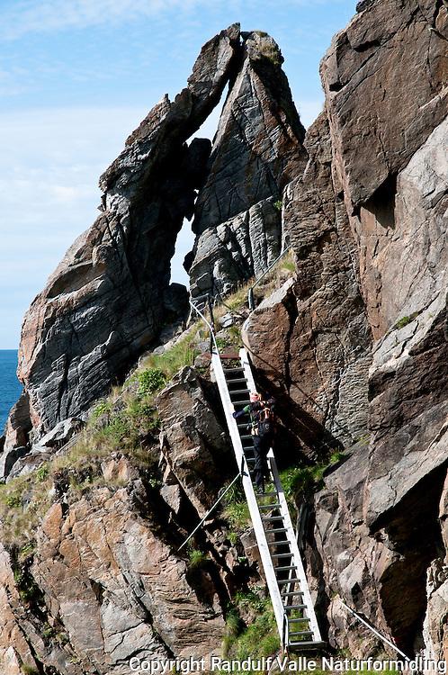 Dame med ryggsekk klarter stige på fyrvokterveien på Tarhalsen, Sørøya. ---- Woman climbing ladder on Sørøya.