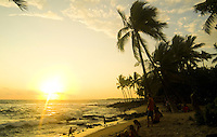 A family watches the glowing sunset at sandy palm tree lined Hano beach in Kona on the Big Island of Hawaii.